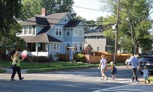 Crossing guard helps family cross the street on first day of school.