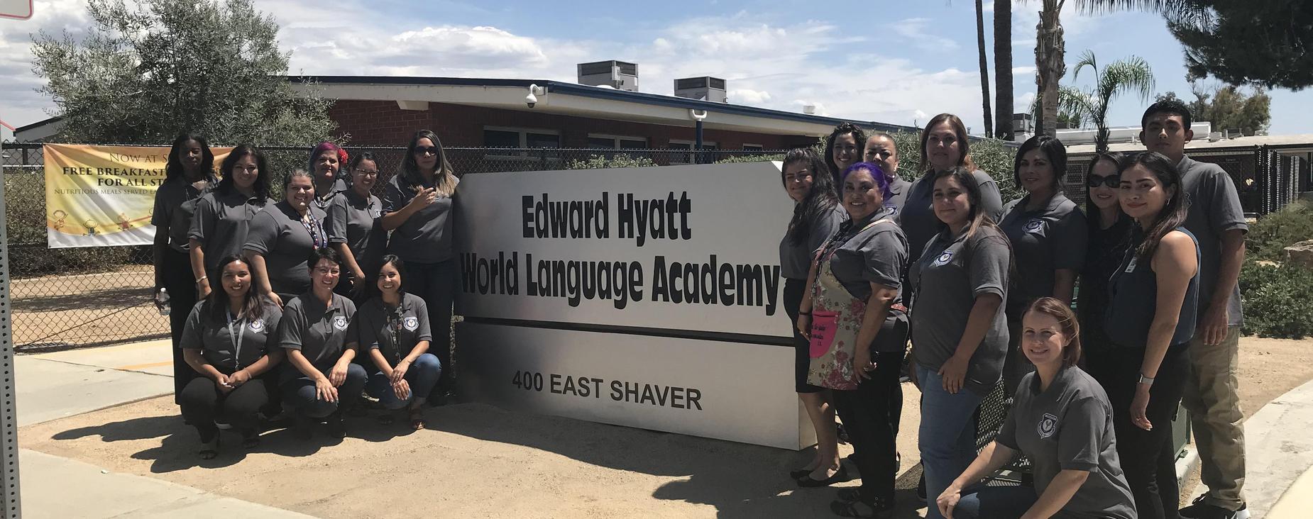 EHWLA Teacher's posing infront of their school name plaque