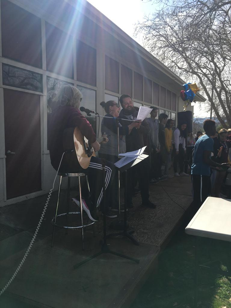 teacher playing guitar and other teachers singing