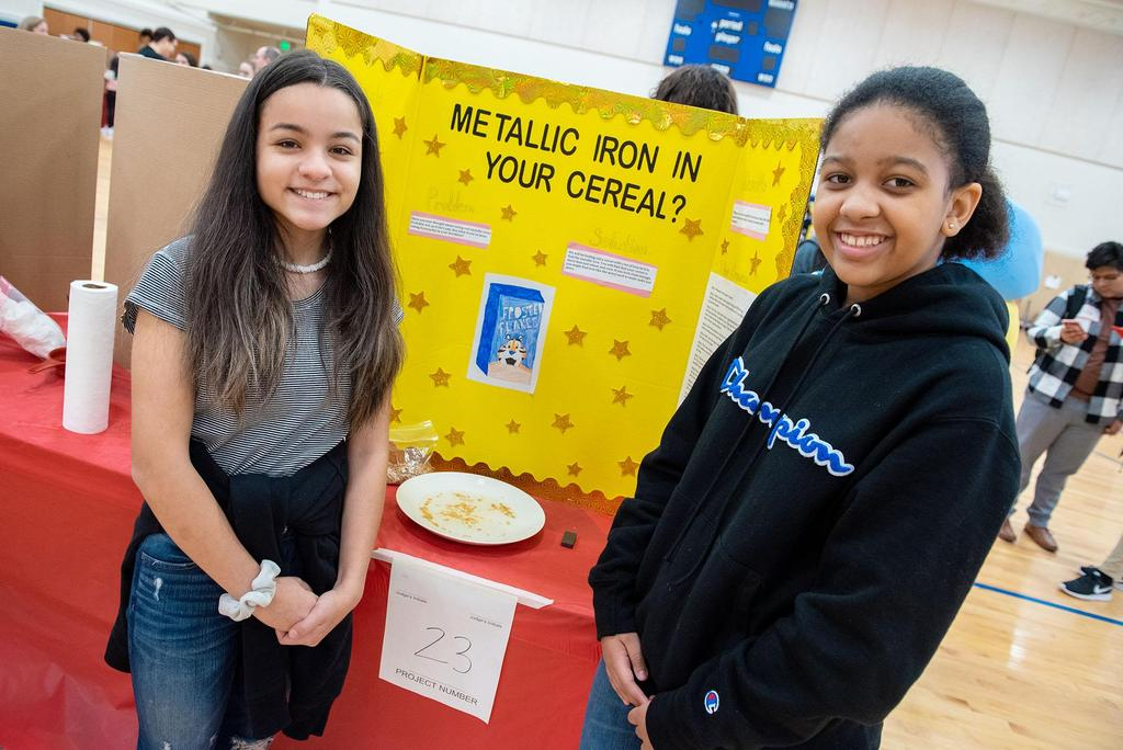 Two girls stand in front of their project called Metallic Iron in Your Cereal?