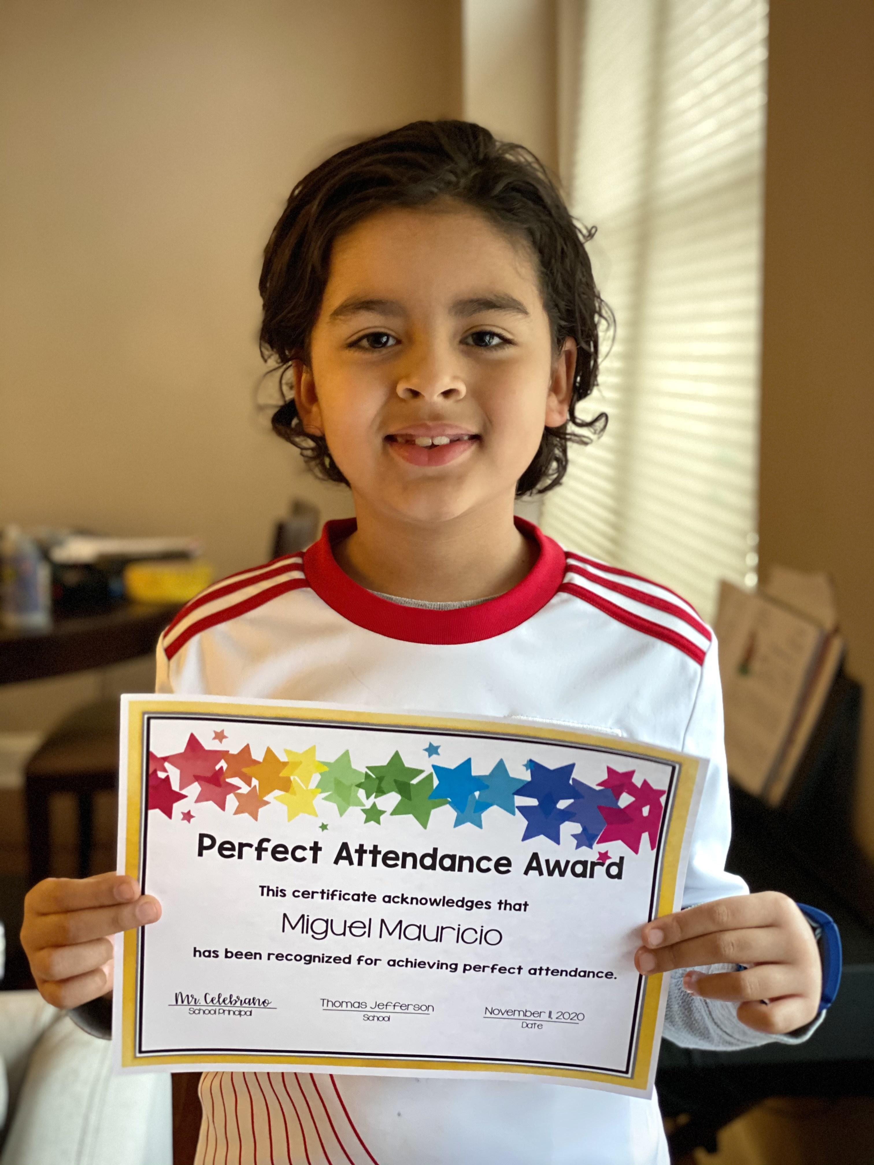 Miguel Mauricio holding perfect attendance certificate
