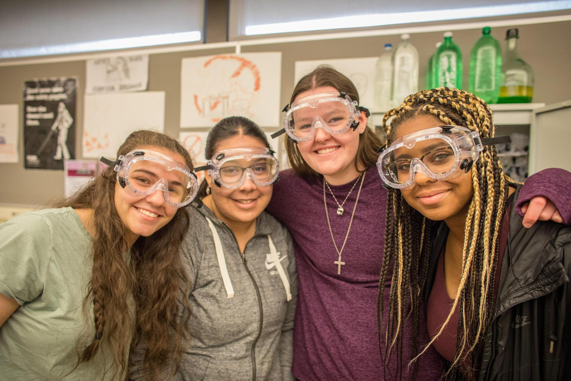 four students smiling in science googles