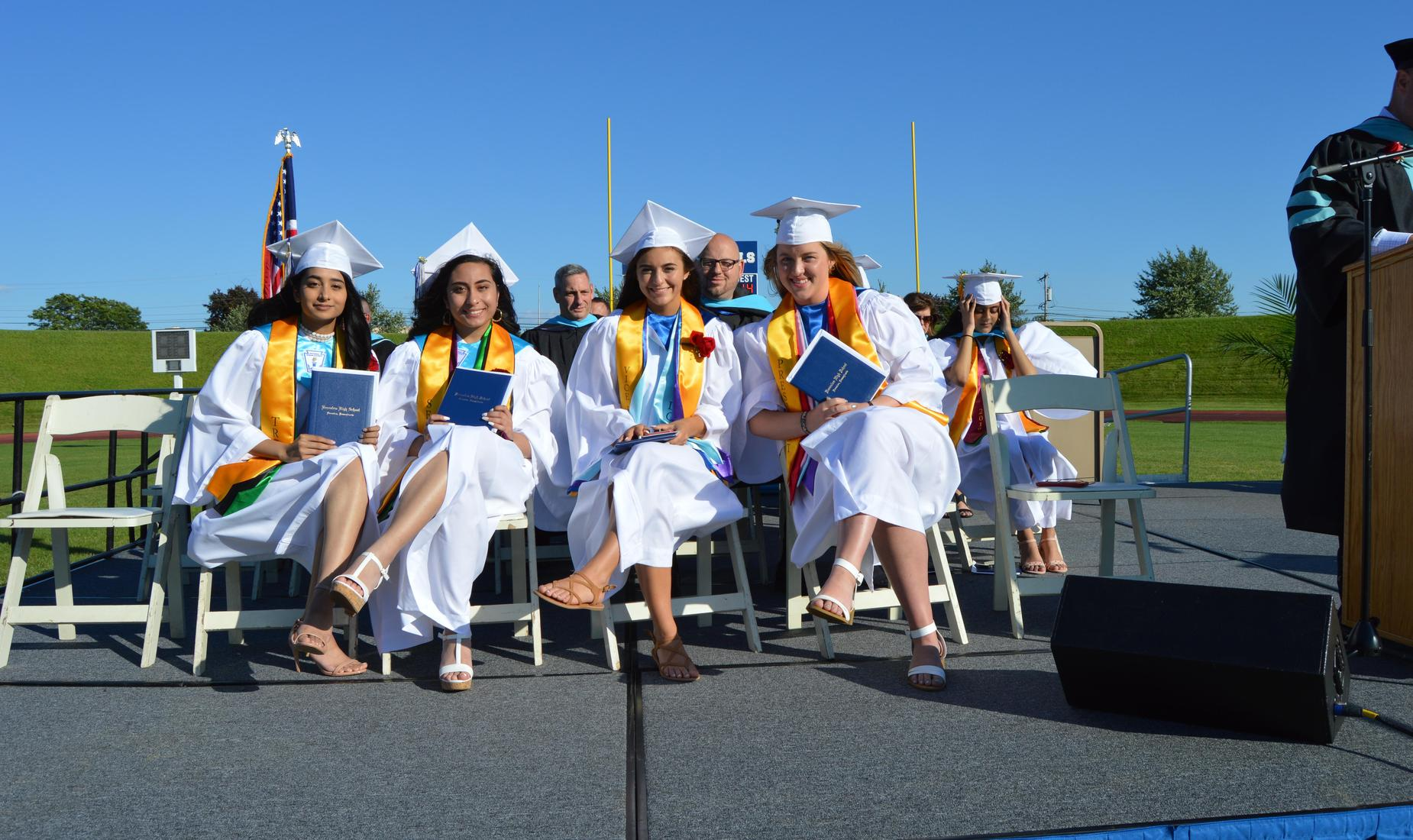 Class of 2019 officers dressed in their white graduation gowns sitting on the dias during the commencement