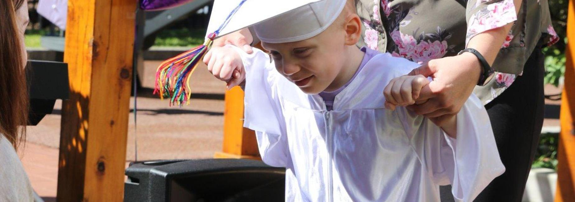 student accepting his preschool graduation diploma