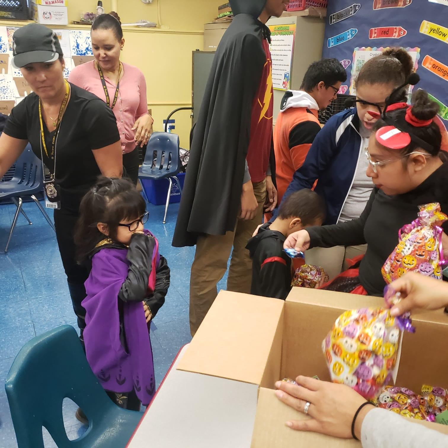 high school students handing out goodie bags to kindergarten student