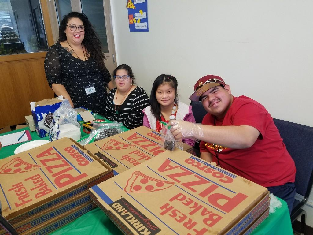 Students sitting at table selling snacks