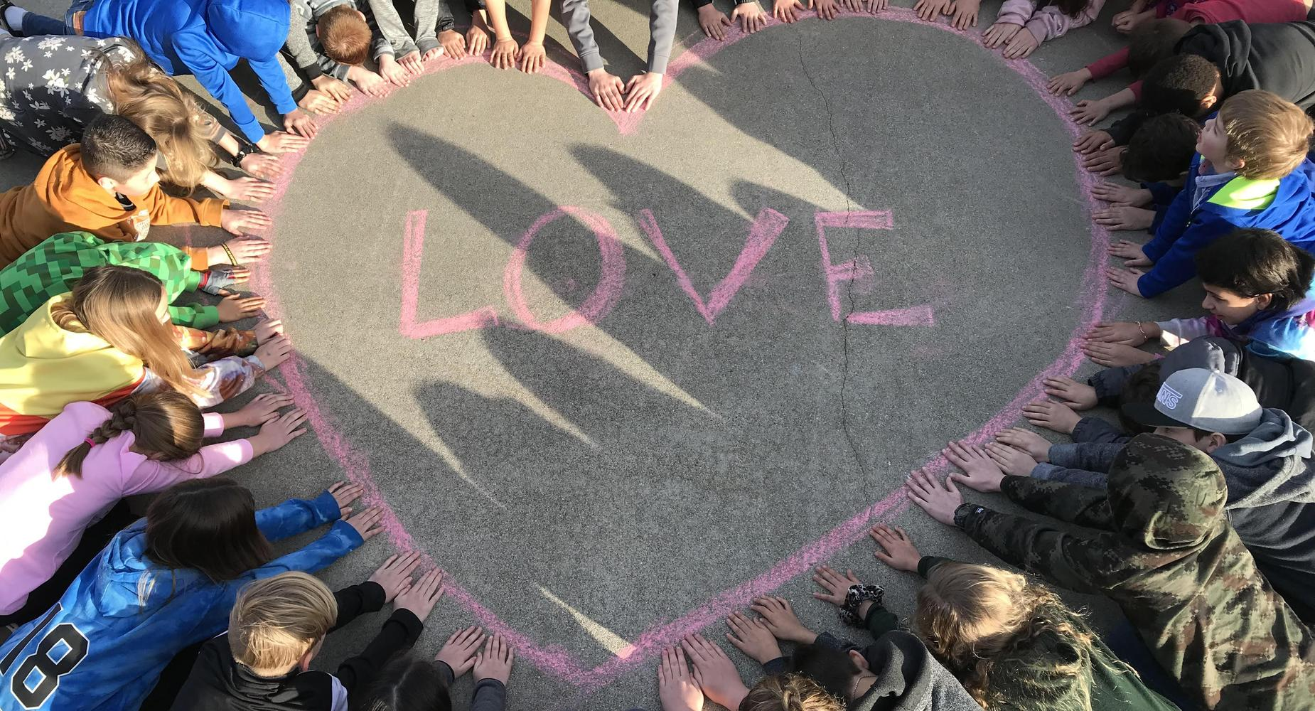 Picture of students with their hand on a giant chalk heart drawing