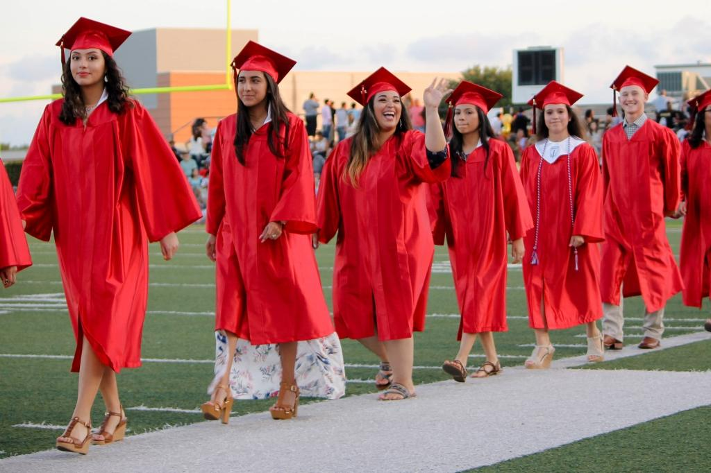 students of the victoria east high school 2018 graduating walking into memorial stadium, smiling female student waiving to the stadium