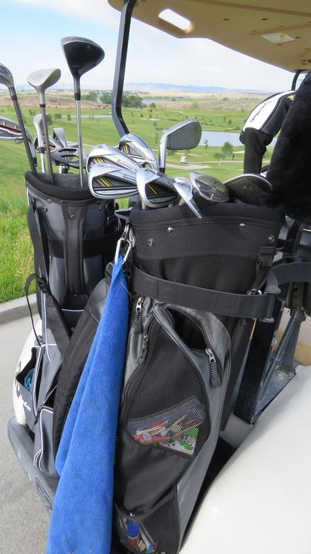 A golf bag with a view of the golf course behind.