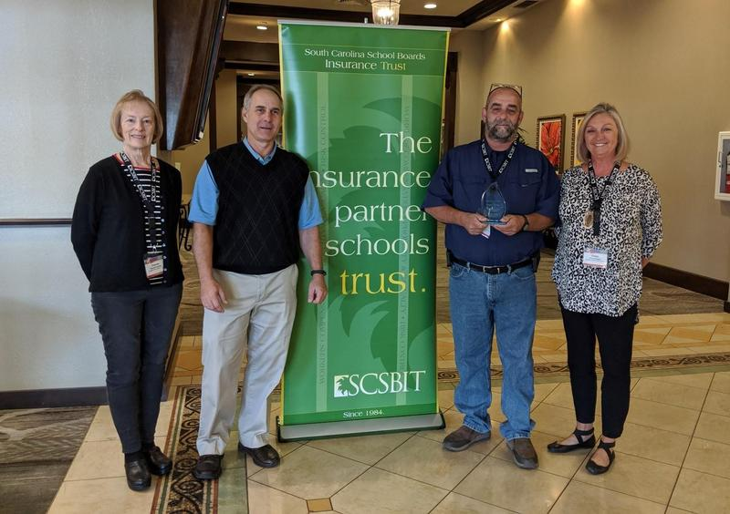 Lexington County School District Three School Board member Frances Bouknight, Director of Maintenance Robby Leaphart and School Board member Cheryl Burgess receive an Excellence in Risk Control award from SCSBIT Risk Control Manager Tim Hinson.