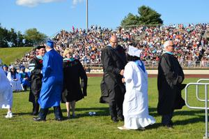 Administrators congratulate the graduates as they walk off the dais to the take their seat on the field