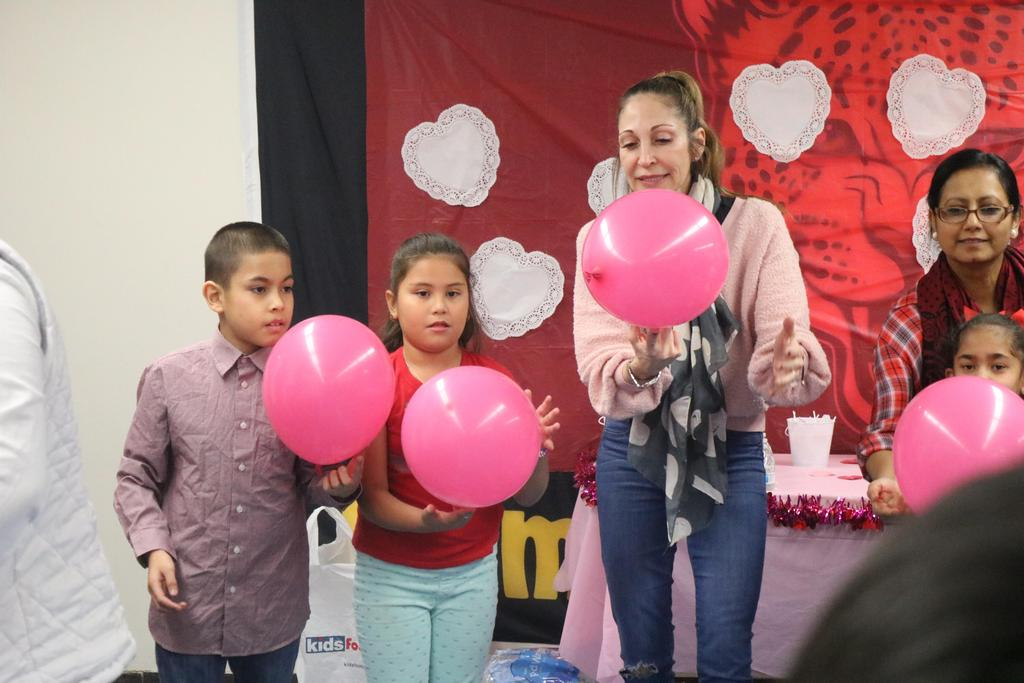 A boy, girl, and teacher each holding a pink balloon in their hands