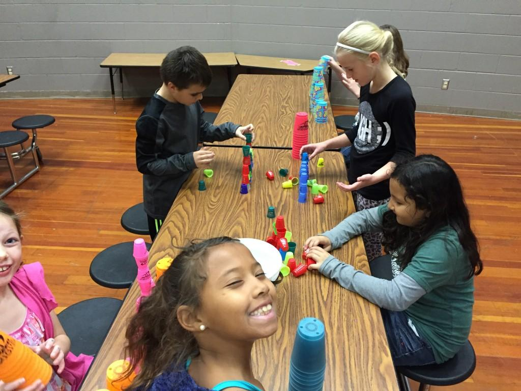 students compete to stack cups in gym