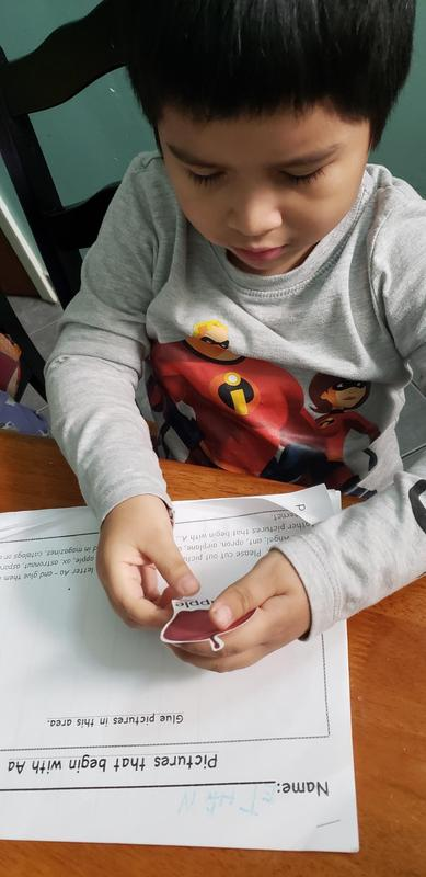 boy in pj's with a sticker in his hand doing his classwork at home