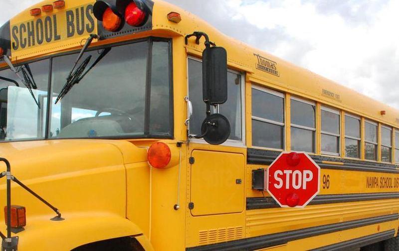 Long view of driver's side of yellow school bus.