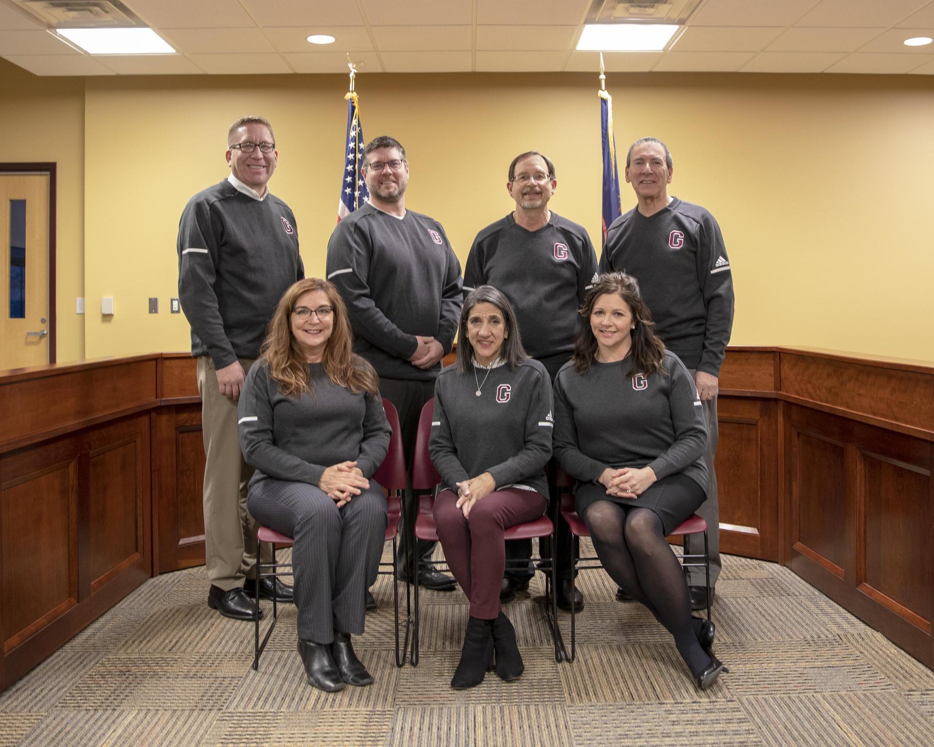 7 board members pose in board room