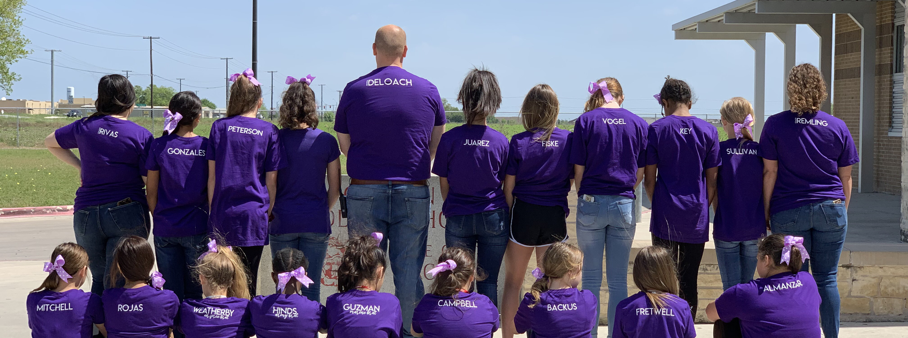 A group of people in purple facing away from the camera