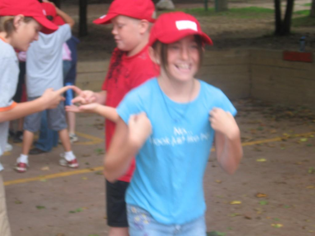student smiling at camp with hands by her armpits