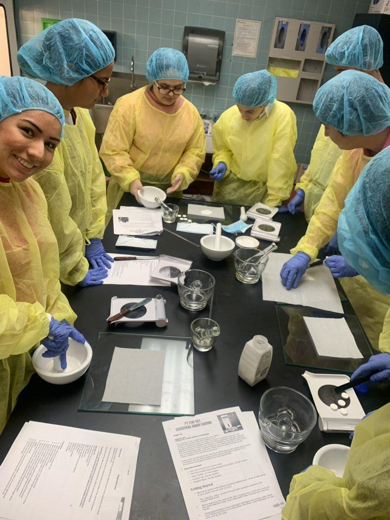 students in medical protective attire working around lab table