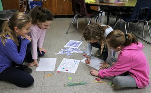 Photo of: Third graders in Elizabeth Reilly's class at Washington School enjoy a game of Spiral Subtraction, using wax sticky twists to create game pieces.