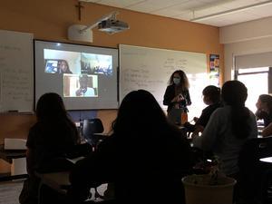 students and teacher watching international speaker