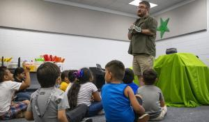man talking to young students