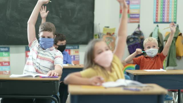 Students with raised hands in classroom