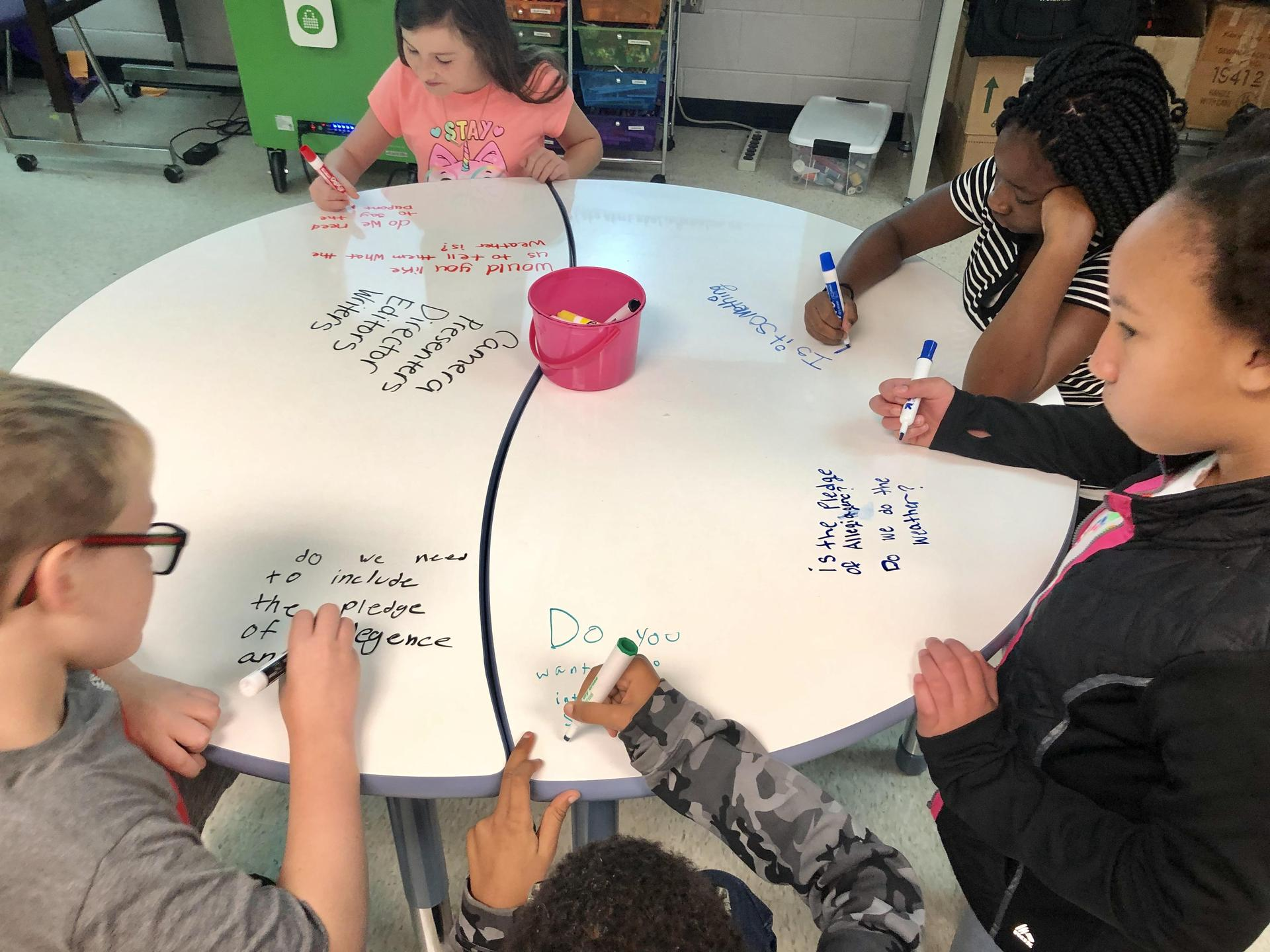 Four children seated and writing on a dry erase table