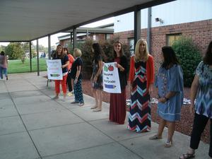 Teachers line the sidewalk and hold signs welcoming students back to school.