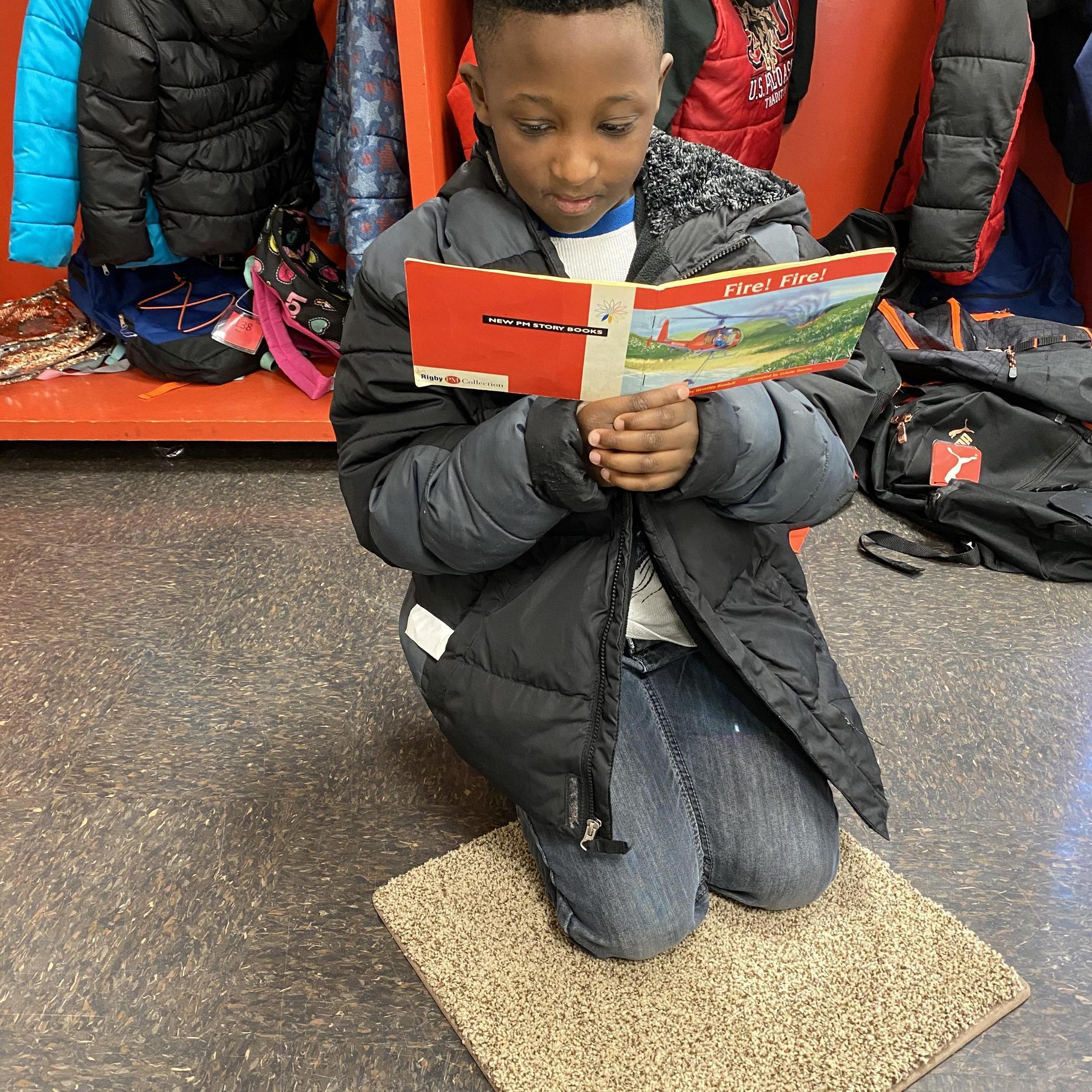 Small boy reading a book.