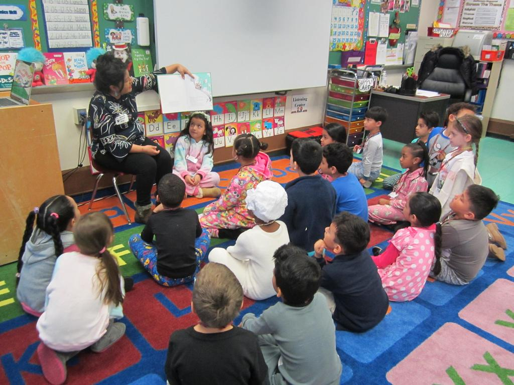 parent volunteer reading to children dressed in pj's sitting on the floor
