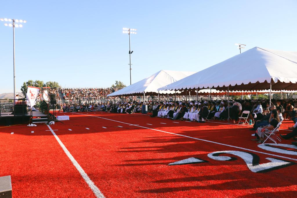 Wide view of Class of 2019 Graduation seating and stage on red football field