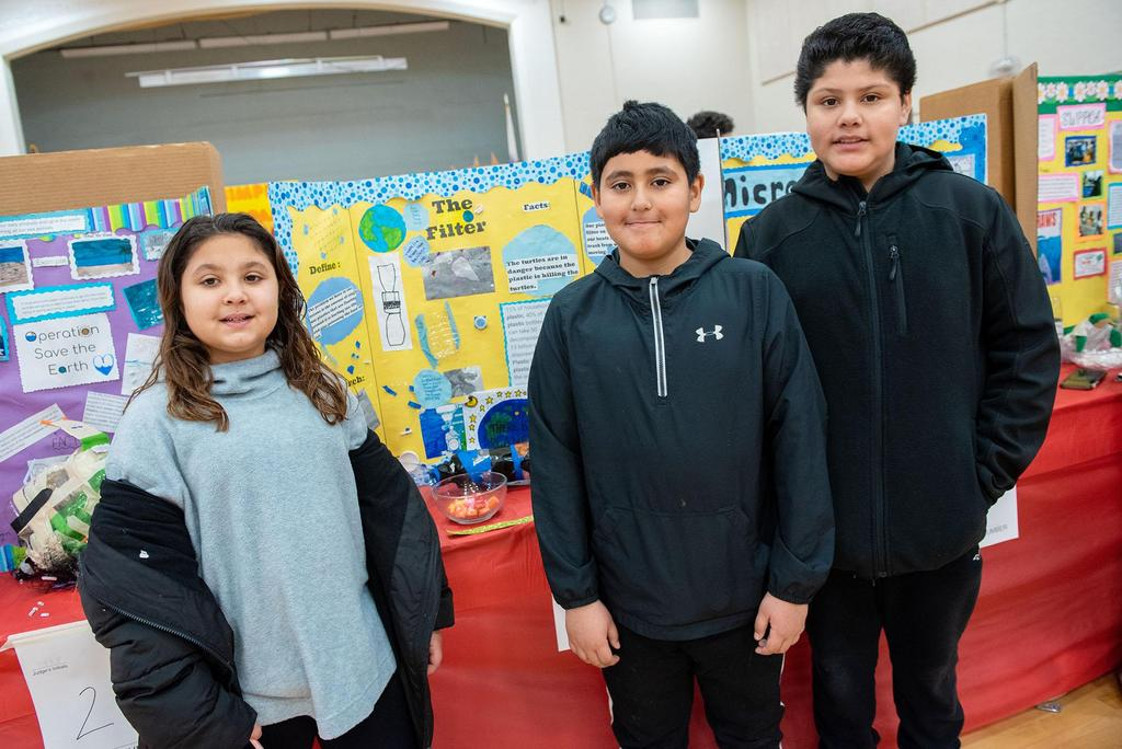 Three students stand in front of their project