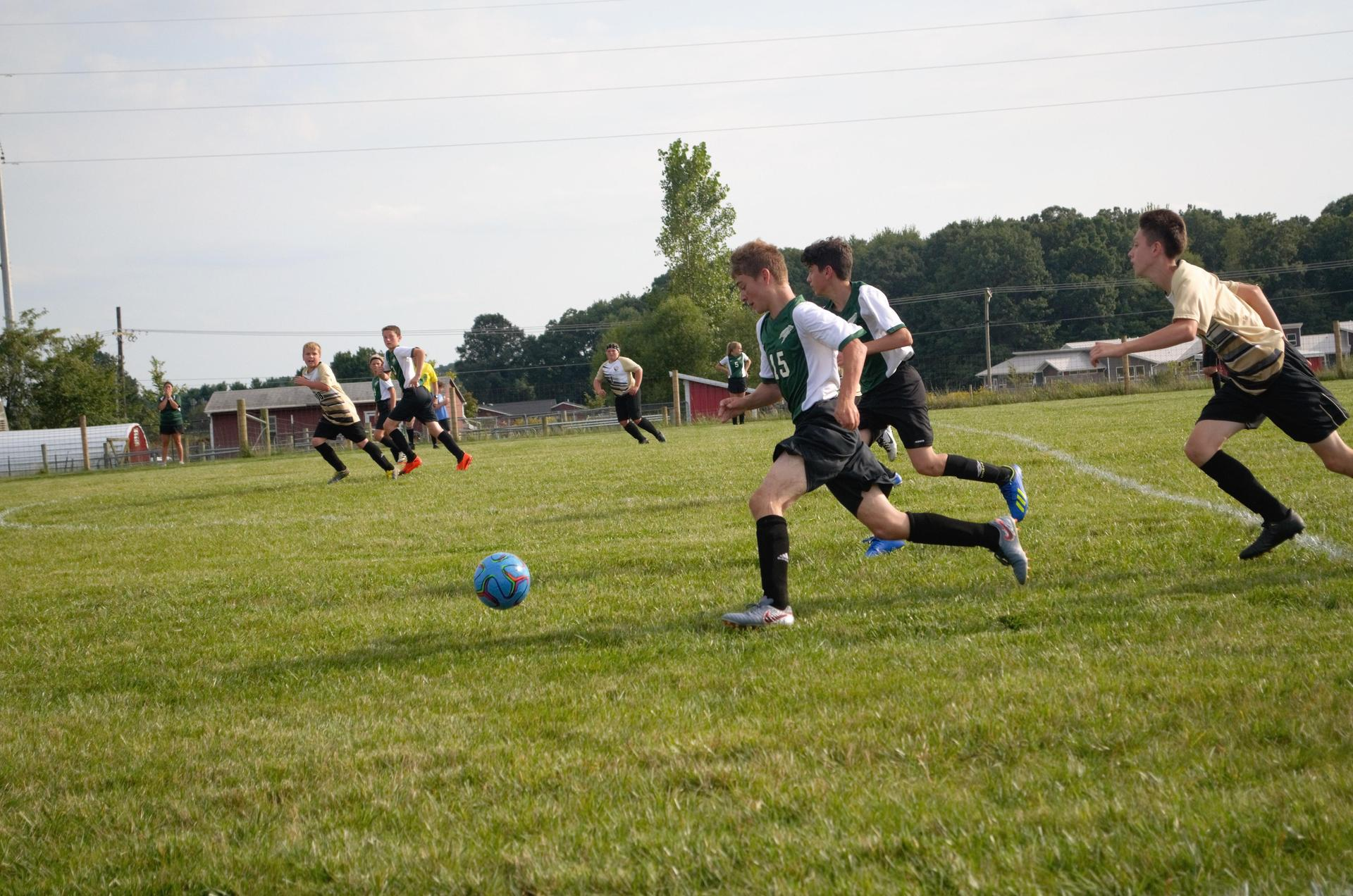 soccer players running for the ball