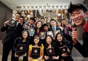 Students in professional attire pose for a picture with their awards.