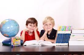 Picture of two boys sitting with books, a globe and other learning materials