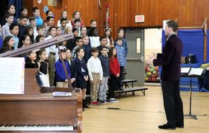 Photo of Tamaques choral director Ben Norkus conducting winter concert.