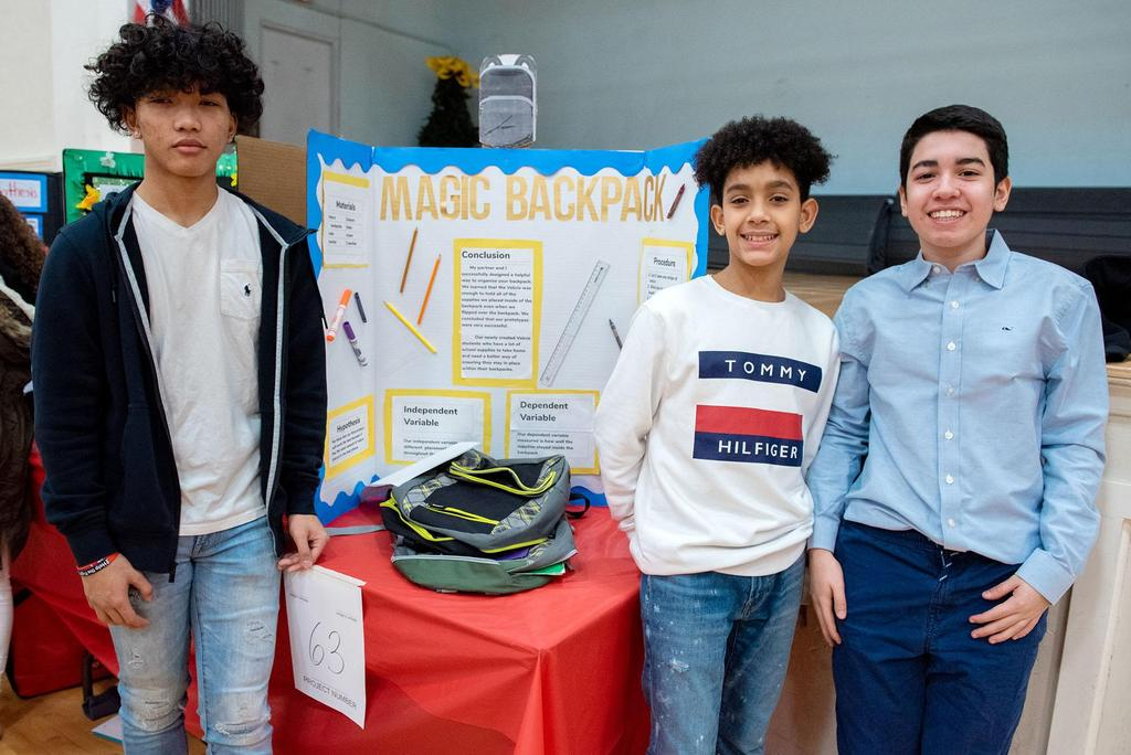 Three students stand with their project The Magic Backpack