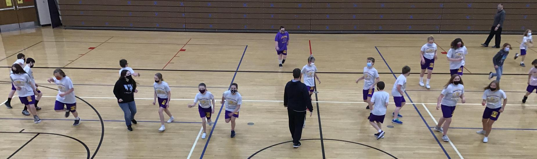 Middle school gym students running in the gym