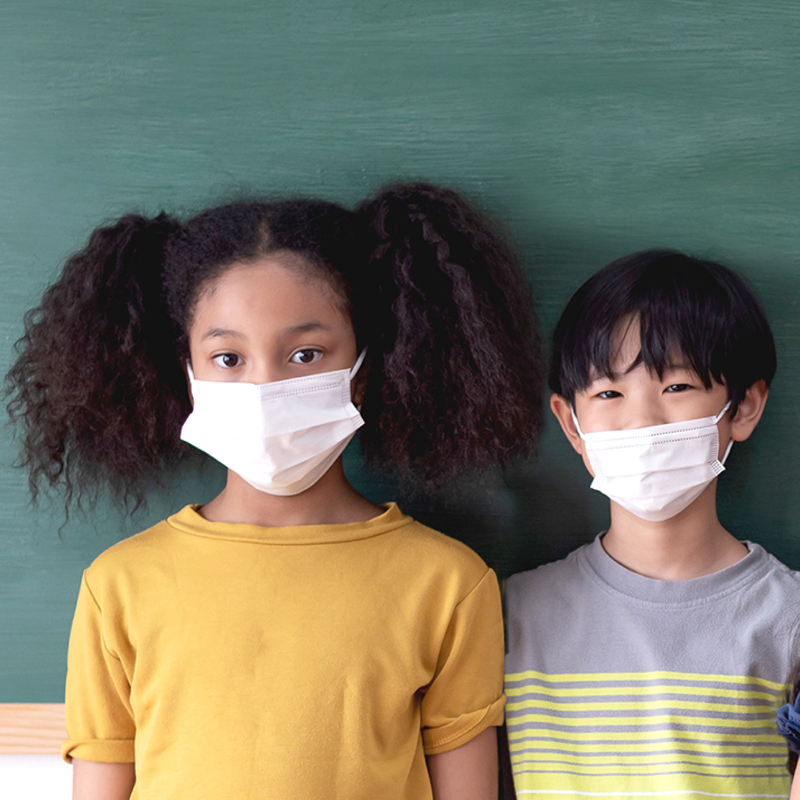 Two elementary age students, a girl and a boy, wearing masks and standing in front of a chalkboard