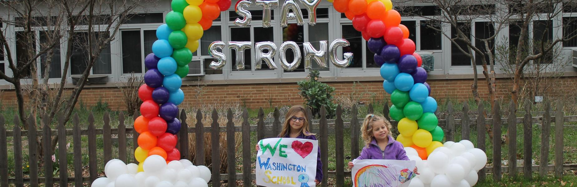 Photo of Washington students in front of rainbow made out of balloons.