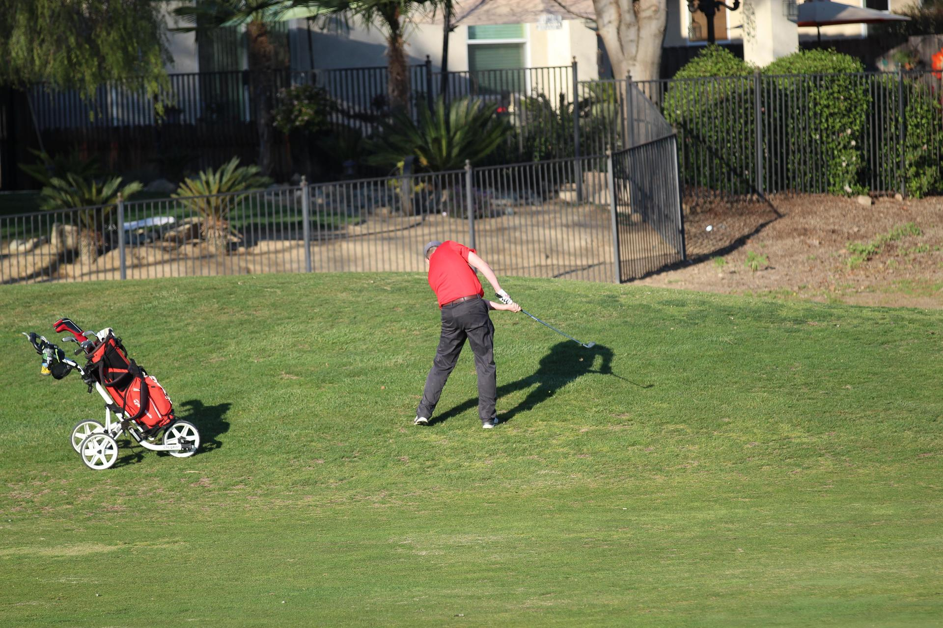 boys playing golf against Los Banos
