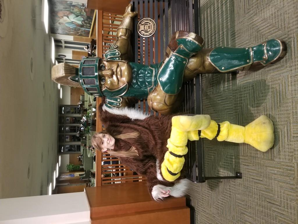 Student in eagle costume sitting with Michigan State Spartan mascot