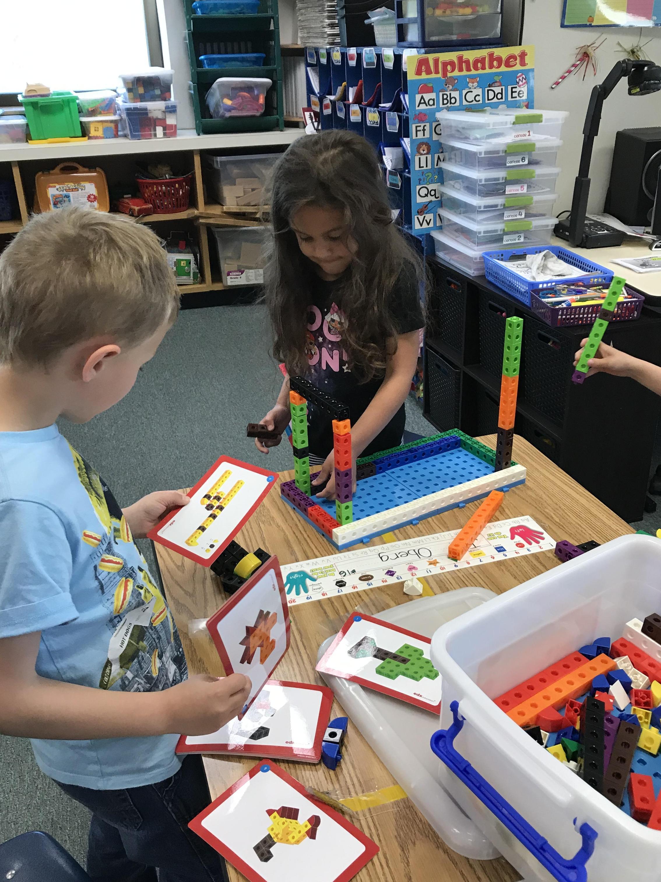 Kindergarten students using STEM materials to build.