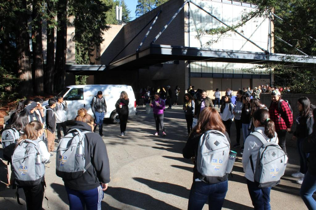 several students with backpacks walking near buildings and trees at UCSC