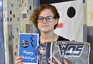 Student holds winning art design and prize