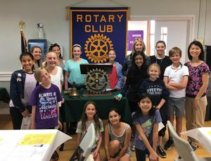 Photo of the Jefferson School Early Act Club posing in front of Rotary Club of Westfield sign with principal Dr. Susie Hung and club advisors.