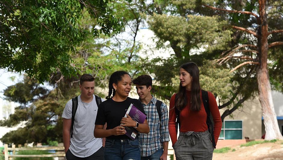 Four upper school students walking through the Quad