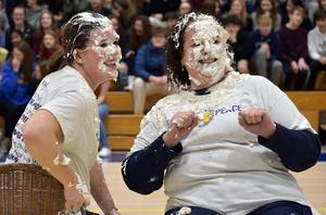 """Middle School teachers Amanda Stavish and Mary Jo Phillips bravely take pies to the face, at the conclusion of a """"Penny Wars"""" fundraiser to benefit Homes for Our Troops."""