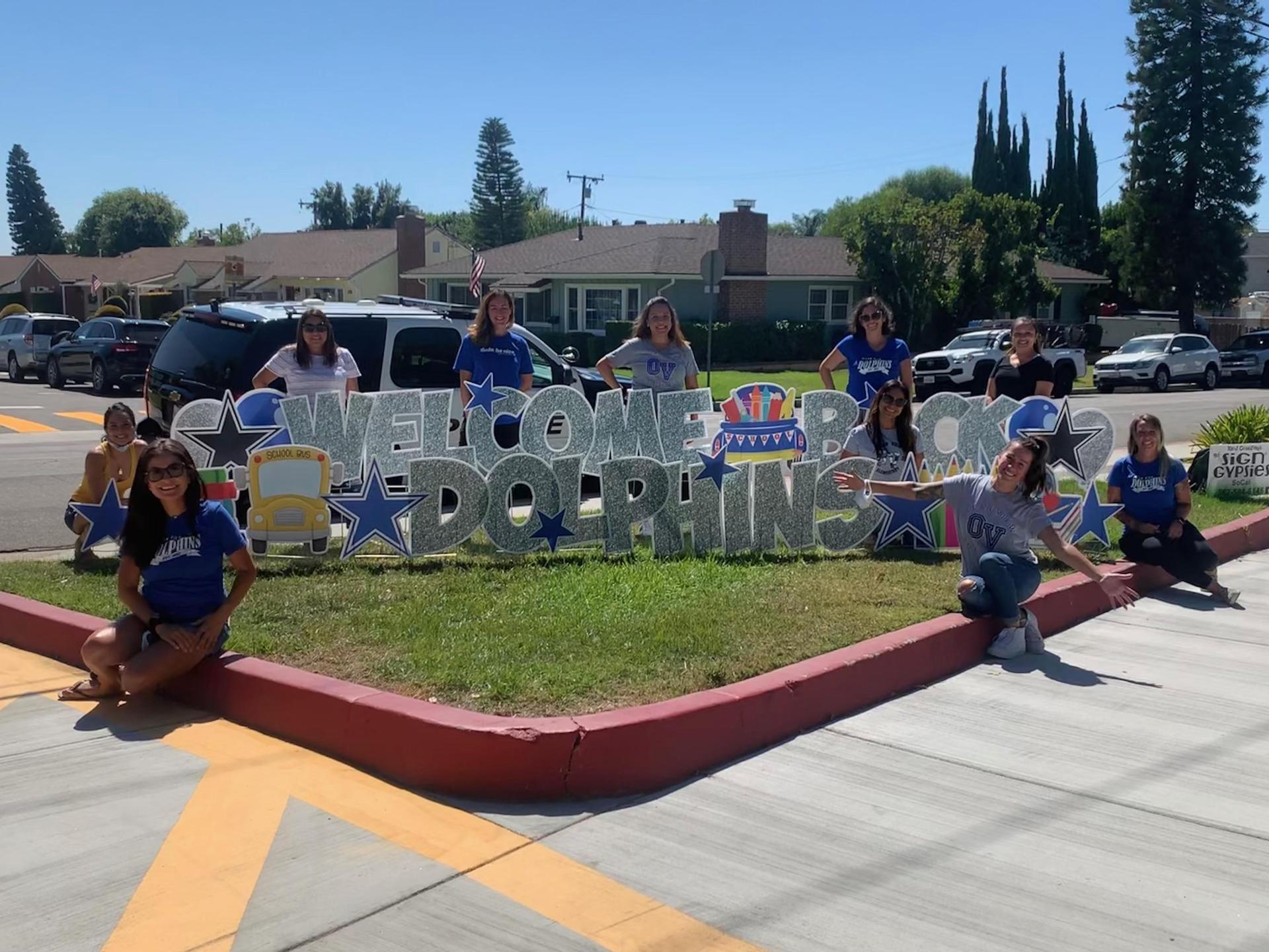 This picture is the PTA Board standing around a sign that says,'Welcome back Dolphins.'
